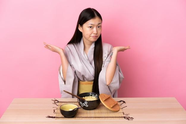 Молодая китайская девушка носить кимоно и есть лапшу, имея сомнения, поднимая руки