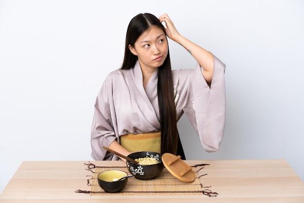 Молодая китайская девушка в кимоно и ест лапшу, сомневаясь, почесывая голову