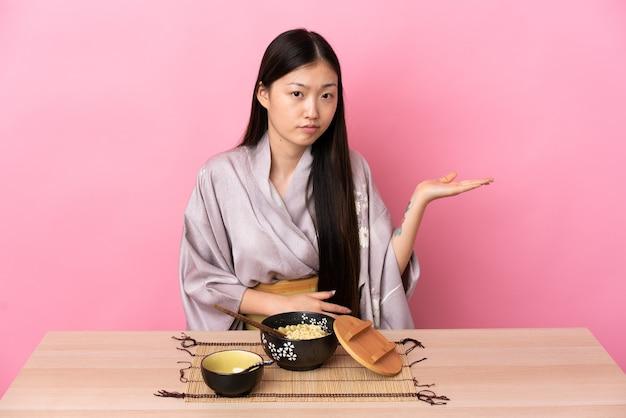 Молодая китайская девушка в кимоно и сомневается в еде лапши