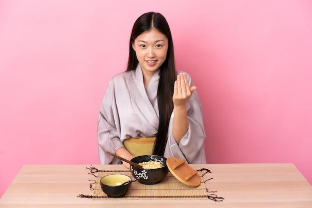 Молодая китаянка в кимоно и ест лапшу, приглашая протянуть руку. счастлив что ты пришел