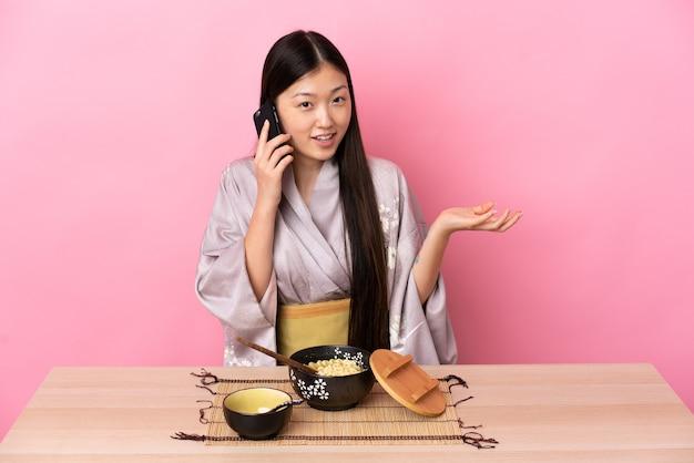Молодая китайская девушка в кимоно и ест лапшу, разговаривая с кем-то по мобильному телефону