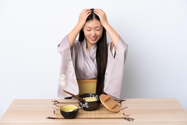 Молодая китайская девушка в кимоно и смеется с лапшой
