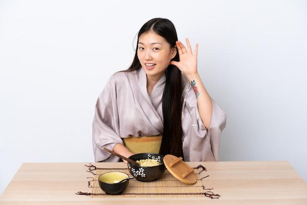 Молодая китаянка в кимоно и ест лапшу, слушая что-то, положив руку на ухо