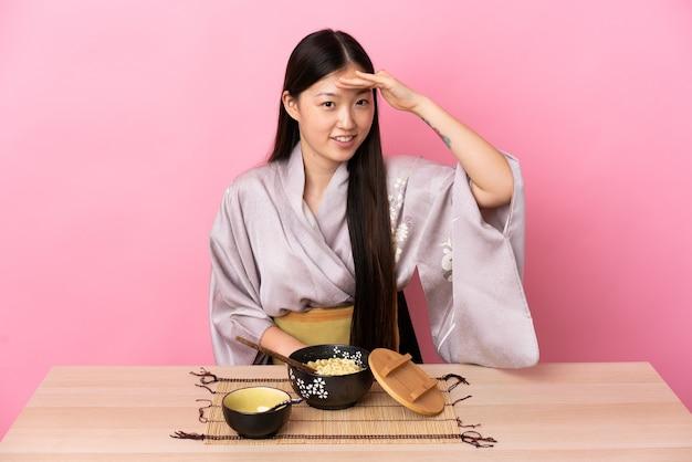 Молодая китаянка в кимоно и ест лапшу, глядя вдаль с рукой, чтобы что-то посмотреть