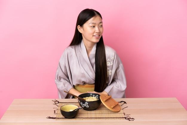Молодая китайская девушка в кимоно и ест лапшу, глядя в сторону