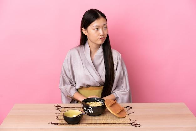 Молодая китаянка в кимоно и ест лапшу, глядя в сторону