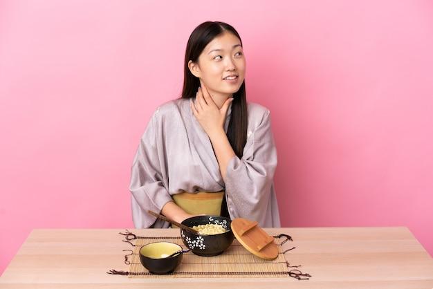 Молодая китайская девушка в кимоно и ест лапшу, глядя вверх, улыбаясь