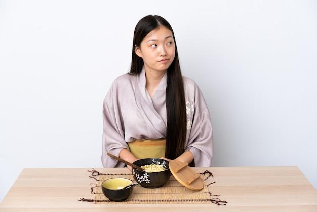 기모노를 입고 국수를 먹는 젊은 중국 소녀는 측면을 찾고 의심 제스처