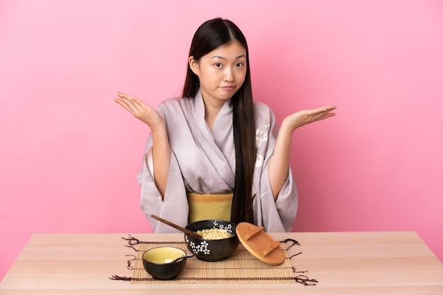 Молодая китаянка в кимоно и ест лапшу, делая жест сомнения
