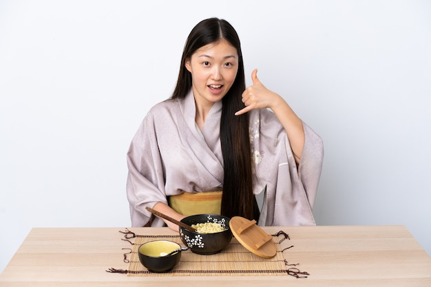 Молодая китаянка в кимоно и ест лапшу, делая жест по телефону. перезвони мне знак