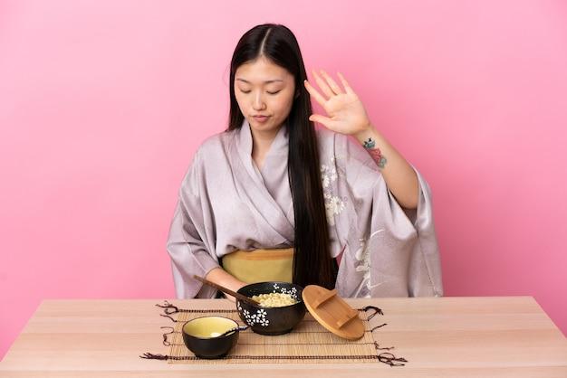 Молодая китаянка в кимоно и ест лапшу, делая жест стоп и разочарованная