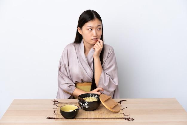 着物を着て、緊張して怖い麺を食べる中国の少女