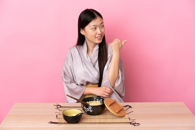 Молодая китаянка в кимоно и ест лапшу, указывая в сторону, чтобы представить продукт