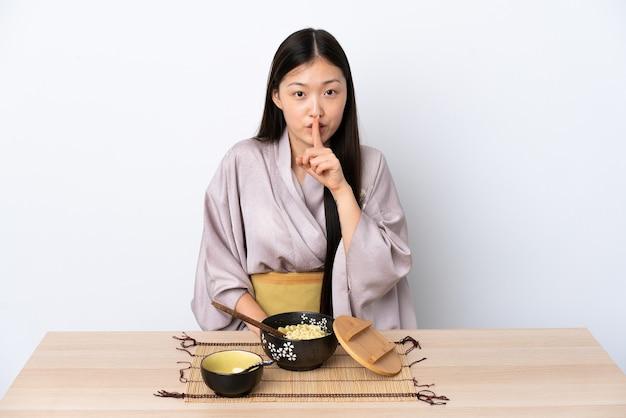 Молодая китаянка в кимоно и ест лапшу, показывая знак тишины, кладя палец в рот