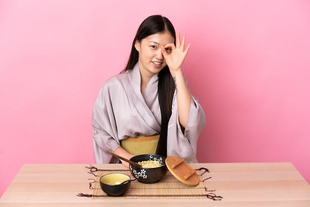 Молодая китаянка в кимоно и ест лапшу, показывая пальцами знак ок