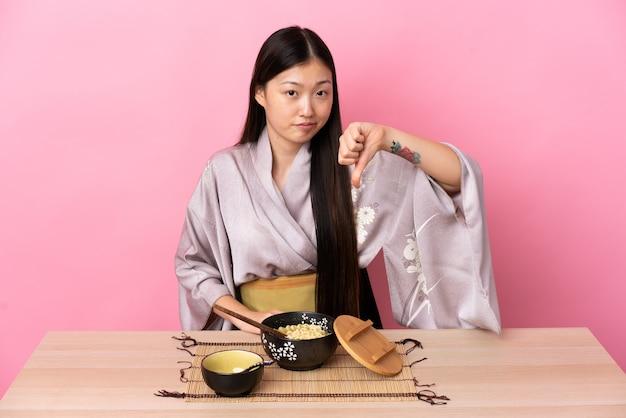 Молодая китаянка в кимоно и ест лапшу, показывая большой палец вниз с отрицательным выражением лица