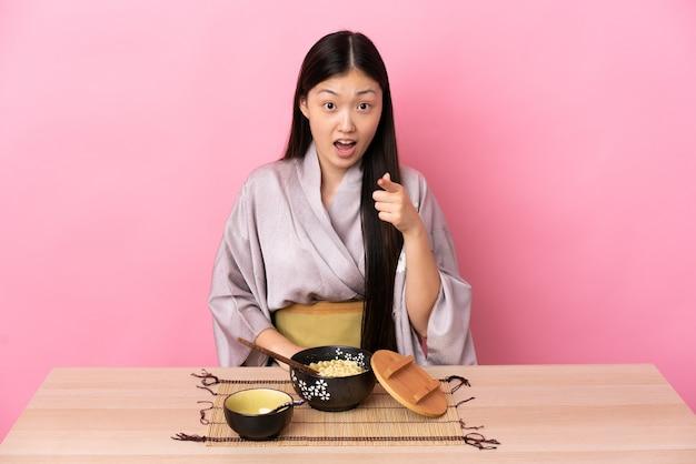 Молодая китаянка в кимоно и ест лапшу удивлена и показывает вперед