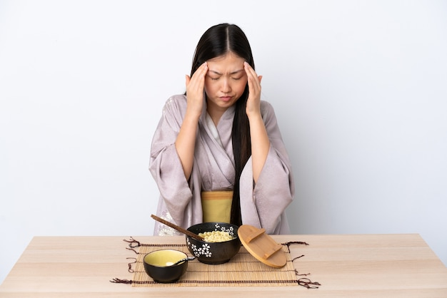 Молодая китаянка в кимоно и ест лапшу с головной болью