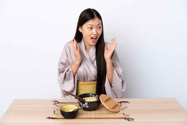 Молодая китаянка в кимоно и с удивленным выражением лица ест лапшу
