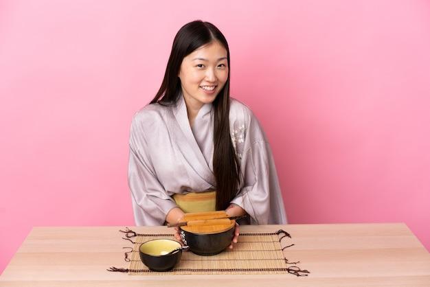 Молодая китайская девушка в кимоно и ест лапшу