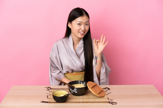 Young chinese girl wearing kimono and eating noodles showing ok sign with two hands