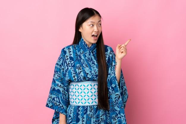 기모노를 입고 젊은 중국 여자는 손가락을 들어 올리는 동안 솔루션을 실현