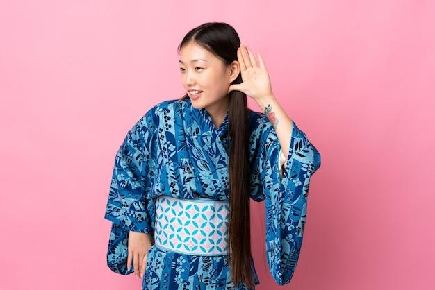 Молодая китаянка в кимоно изолировалась от чего-то, положив руку на ухо