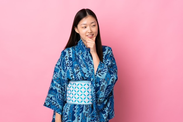 Young chinese girl wearing kimono looking to the side and smiling