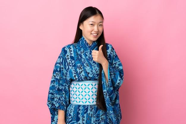 제스처를 엄지 손가락을주는 격리 된 배경 위에 기모노를 입고 젊은 중국 소녀