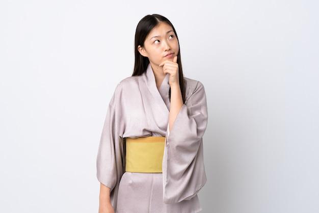 의심을 갖는 고립 된 배경 위에 기모노를 입고 젊은 중국 소녀