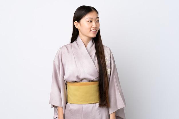 Молодая китайская девушка в кимоно на изолированном фоне, глядя в сторону
