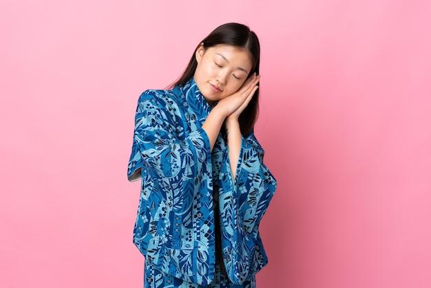 Dorable 식에서 수면 제스처를 만드는 격리 된 배경 위에 기모노를 입고 젊은 중국 소녀
