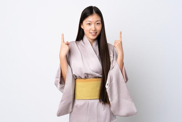 Молодая китаянка в кимоно на изолированном фоне указывает на отличную идею