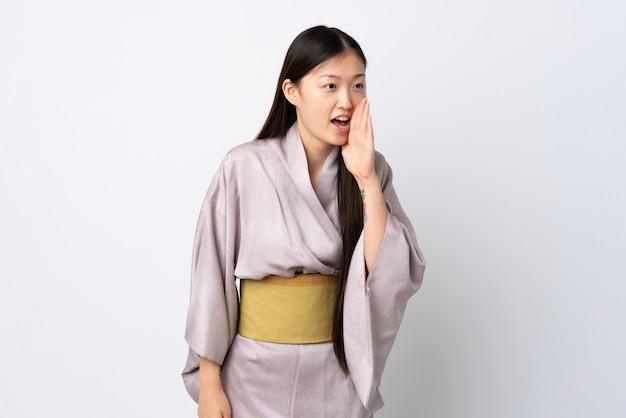 격리 된 배경 위에 기모노를 입고 어린 중국 소녀 입 벌리고 옆으로 외치는