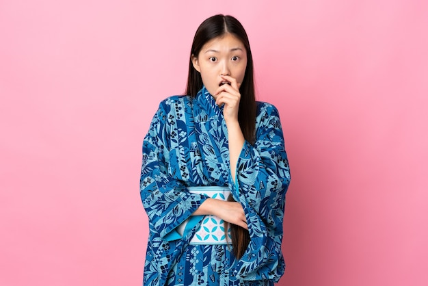 격리 된 배경 위에 기모노를 입고 젊은 중국 소녀는 바로보고있는 동안 놀라게하고 충격을 받았습니다.