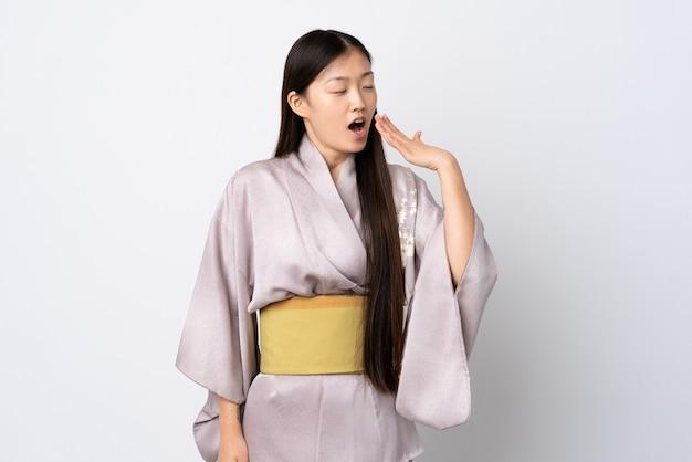 あくびをし、手で大きく開いた口を覆う孤立した背景の上に着物を着ている若い中国の女の子