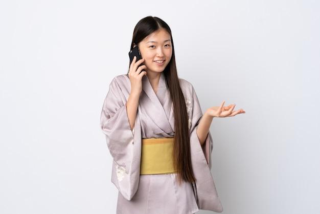 誰かと携帯電話で会話を続けている孤立した上に着物を着ている若い中国の女の子