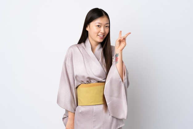 孤立した笑顔と勝利のサインを示す上に着物を着ている若い中国の女の子