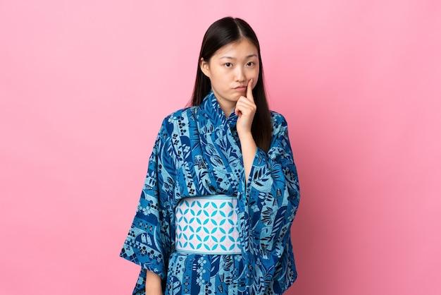 고립 된 벽과 생각에 기모노를 입고 젊은 중국 소녀