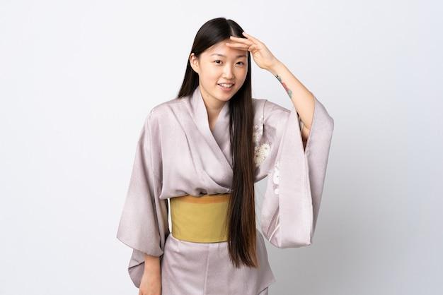何かを見るために手で遠くを見ている孤立した壁の上に着物を着ている若い中国の女の子