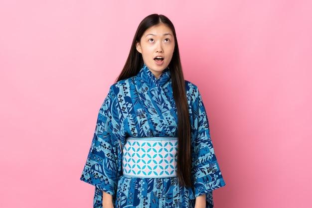 고립 된 벽 위에 기모노를 입고 젊은 중국 소녀를 찾고 놀란 표정으로