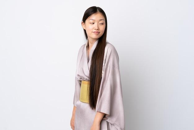 Молодая китаянка в кимоно над изолированной стеной. портрет