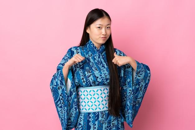 誇りと自己満足の孤立した壁に着物を着ている若い中国の女の子