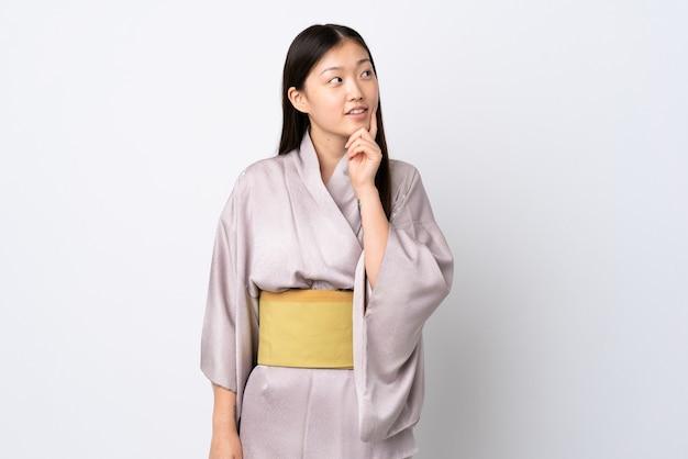 찾는 동안 아이디어를 생각하는 고립 된 벽 위에 기모노를 입고 젊은 중국 소녀