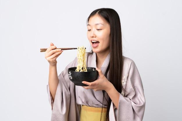 Молодая китаянка в кимоно на изолированном белом фоне держит миску лапши с палочками для еды и ест ее