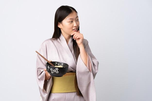 孤立した白い背景の上に着物を着てアイデアを考え、箸で麺のボウルを保持しながら横を見て若い中国の女の子