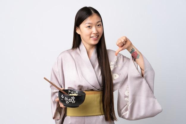 Молодая китаянка в кимоно над изолированной белой стеной, гордая и самодовольная, держа миску лапши с палочками для еды