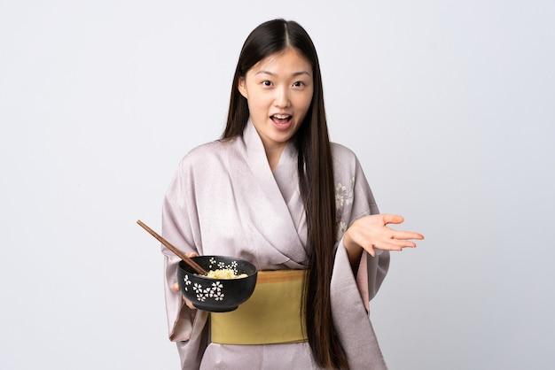 箸で麺のボウルを保持しながら、ショックを受けた表情で孤立した白の上に着物を着ている若い中国の女の子