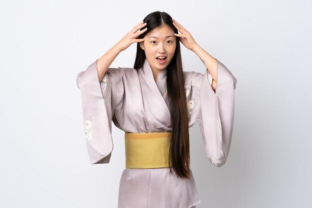 驚きの表情で孤立した上に着物を着ている若い中国の女の子