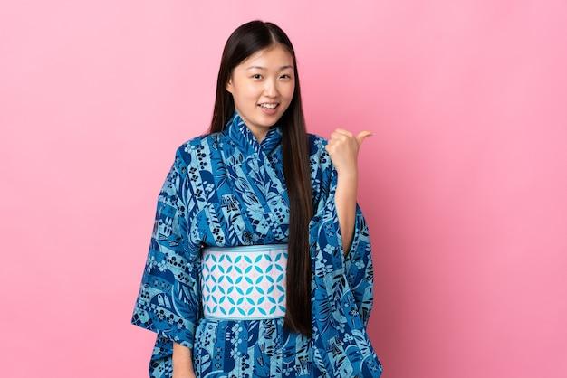 製品を提示するために横を指して着物を着ている若い中国の女の子